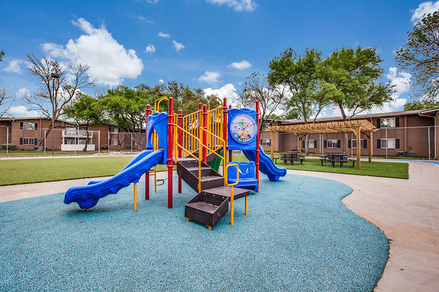 Playground with green space, picnic tables and pergola.