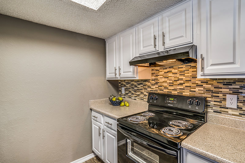 Black appliance package, new cabinetry, and mosaic tile backsplash in upgraded apartments.