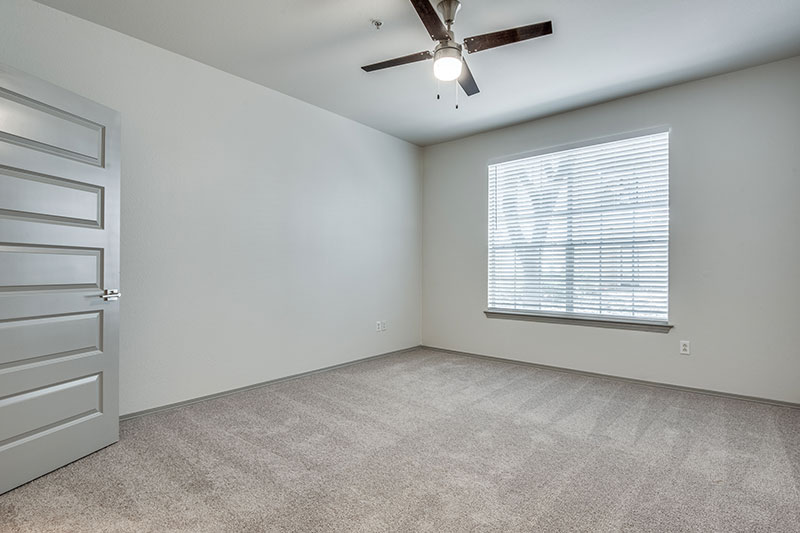 Spacious bedroom with expansive walk-in closet and ceiling fan.