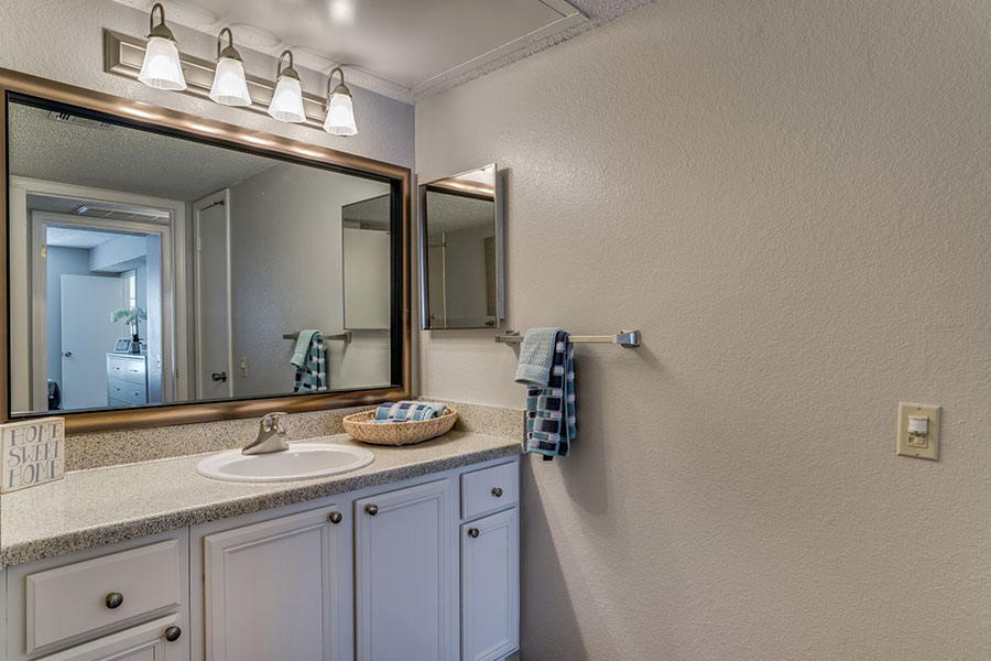 Designer bathrooms with accent framed mirror.