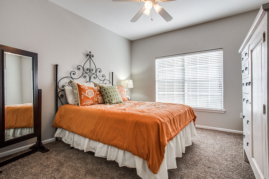 Spacious bedroom with large window, ceiling fan and carpet.