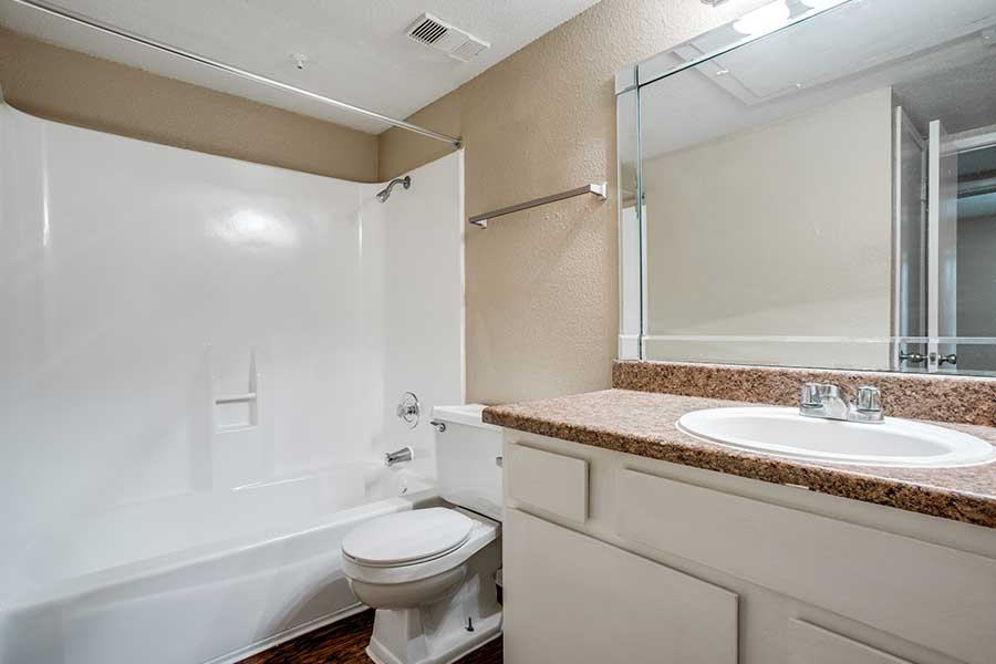 The sleek bathrooms feature a large tub and a decorator accent mirror over the bathroom sink.