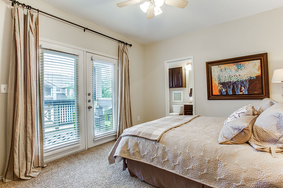 Spacious bedroom with en-suite that includes access to the balcony, ceiling fan, and large walk-in closet.